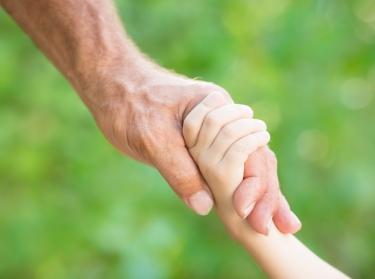 Senior man holding child's hand outdoors