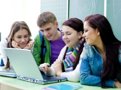 Group of young students studying in the classroom with a laptop
