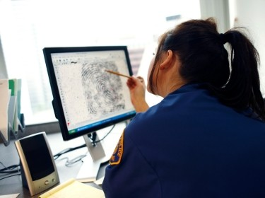 A police officer examining a fingerprint on a monitor