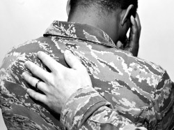A U.S. Air Force Airman places his hand on another Airman's back at Shaw Air Force Base, S.C., November 21, 2014