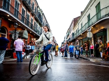 A woman rides her bike as people walk through the French Quarter in New Orleans
