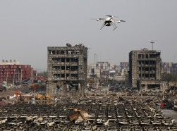 A drone operated by paramilitary police flies over the site of explosions at Binhai new district in Tianjin, China, August 17, 2015