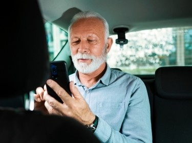 Older man in the backseat of a car looking at his smartphone, photo by Nastasic/Getty Images
