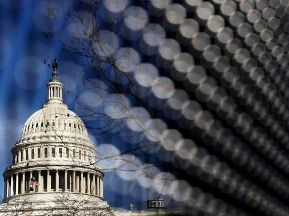 Light catches the security fence around the U.S. Capitol, erected in the wake of the January 6th attack but now scheduled to be removed, in Washington, D.C., March 15, 2021, photo by Jonathan Ernst/Reuters