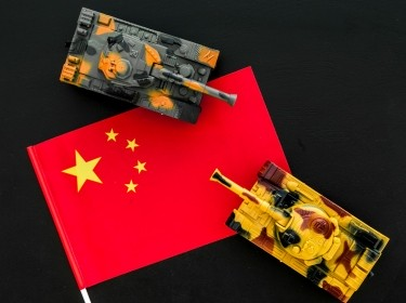 War, military threat, military power concept. China. Tanks toy near chinese flag on black background top view, photo by 9dreamstudio/AdobeStock