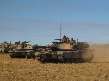 Australian Army M1 Abrams Tanks with 1st Armored Brigade, assault an enemy position during Exercise Koolendong at Bradshaw Training Area, Aug 21, 2014. Four Marines with 1st Bn., 5th Marines, were given an opportunity to support elements of 5th Battalion, Royal Australian Regiment and 1st Armored Brigade. During Exercise Koolendong 2014, approximately 1500 Marines and Australian Defence Force soldiers will undertake a wide spectrum of infantry training activities to include establishing an expeditionary operating base in austere conditions, company-sized helicopter and ground live-fire ranges, photo by Sgt. James Gulliver