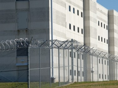 The exterior wall of a prison surrounded by barbed wire fence. Photo by eddiesimages / Getty Images