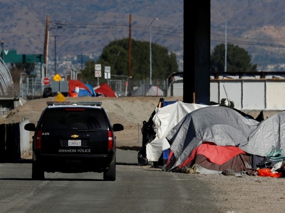 Police continue their patrols as officials begin what they are calling a slow and methodical clean-up and removal of a large homeless encampment along the Santa Ana River Trail in Anaheim, California, January 22, 2018, photo by Mike Blake/Reuters