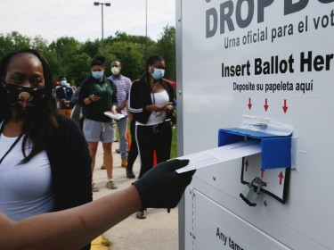 Maryland election judge Cassandra Campbell watches a voter place a ballot in a drop box, College Park, Maryland, June 2, 2020, photo by Jim Bourg/Reuters