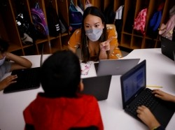 Teacher Mary Yi works with fourth-grade students at the Sokolowski School in Chelsea, Massachusetts, September 15, 2021, photo by Brian Snyder/Reuters