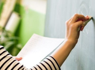 Teacher writing on a blackboard, photo by Andrea Obzerova/Adobe Stock