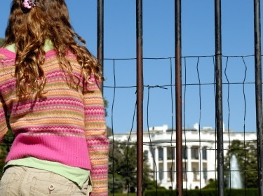 A teenage girl looks through a fenced barrier in front of the White House, photo by EyeJoy/Getty Images