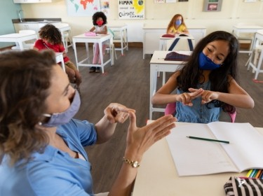 A teacher and student wearing face masks talk to each other using sign language, photo by Wavebreakmedia/Getty Images