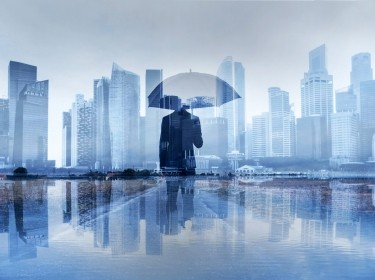 A business person in a suit holding an umbrella in front of a cityscape. Photo by anyaberkut / Getty Images