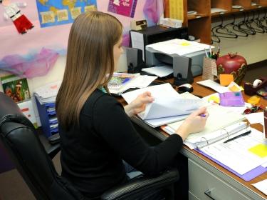 Teacher grading papers in elementary school WFT, photo by bonniemarie/AdobeStock