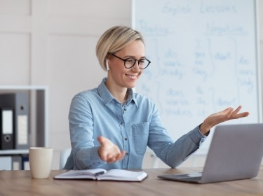 Experienced English teacher giving online lesson on laptop, chatting with students, participating in webinar from home, photo by Prostock-studio/Adobe Stock