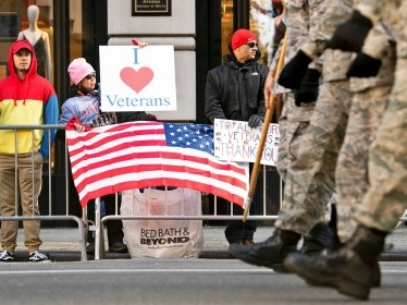Spectators hold signs supporting veterans along the 2018 Veterans Day Parade route in New York City, November 11, 2018, photo by EJ Hersom/Department of Defense