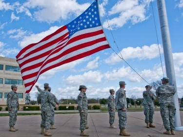 A formation of U.S. Army soldiers with III Corps and Fort Hood honor the American flag as they lower it during the Retreat ceremony, March 27, 2014, photo by U.S. Army