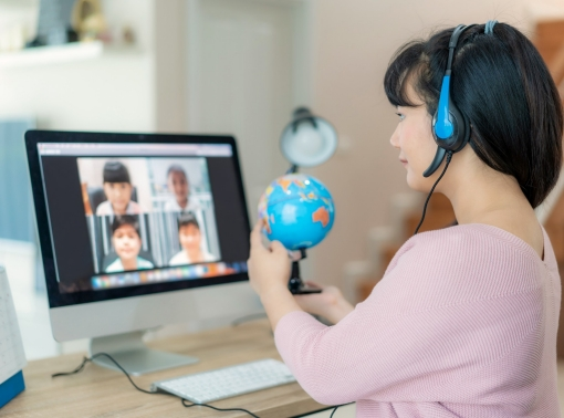 A teacher showing a globe to her online elementary students, photo by ake1150sb/Getty Images