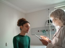 Doctor talking to patient at hospital room with a digital tablet, photo by FG Trade/Getty Images
