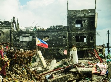 Photograph image of Philippine flag standing on a war torn city of Marawi in the Philippines.