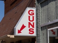 A gun store sign with a red arrow pointing downwards. Photo by jetcityimage / Getty Images