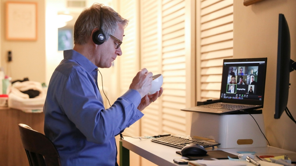 Doug Hassebroek eats breakfast while on a video conference call at his home in Brooklyn, April 24, 2020, photo by Caitlin Ochs/Reuters