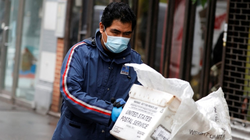 A U.S. Postal Service mail carrier delivers mail in the rain on Manhattan's Upper West Side during the outbreak of COVID-19 in New York City, New York, April 13, 2020, photo by Mike Segar/Reuters