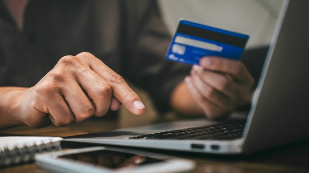A person holds a credit card and types on a laptop while online shopping