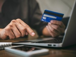 A person holds a credit card and types on a laptop while online shopping, photo by Ngampol/Adobe Stock
