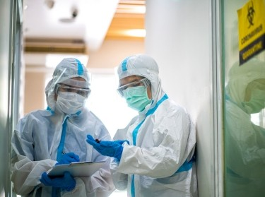 Two health care workers checking on a patient in quarantine, photo by tuachanwatthana/Getty Images
