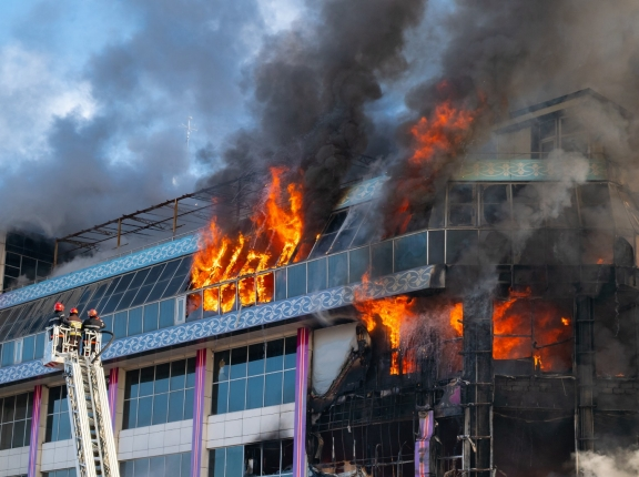 Smoke billowing from a burning building with firefighters on a ladder. Photo by Vastram / Adobe Stock
