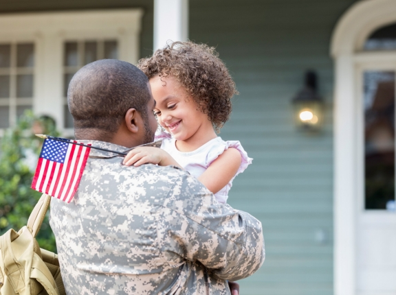 Military veteran hugging his daughter in front of his house, photo by SDI Productions/Getty Images