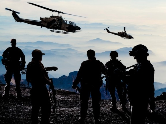Silhouettes of soldiers during Military Mission at dusk, photo by guvendemir/Getty Images