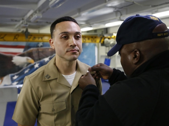 Lt. Brendan Shields, assigned to Pre-Commissioning Unit Gerald R. Ford (CVN 78), is pinned to the rank of lieutenant by Chief Warrant Officer Tony Cochran during a promotion ceremony on Ford's fo c'sle, photo by Chuck Little / Alamy Stock Photo