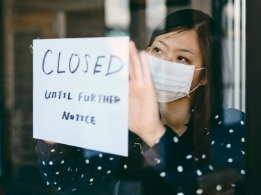 Business owner in a mask posting a closed sign on the door, photo by RichLegg/Getty Images