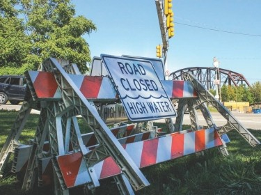 """Traffic barriers with a sign reading """"Road Closed High Water"""" on the roadside near Washington Boulevard, Pittsburgh, PA. Photo by Jordan Fischbach / RAND Corporation"""
