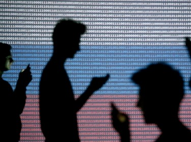 People are silhouetted as they hold mobile devices in front of a screen projected with a binary code and a Russian flag, in Zenica, Bosnia and Herzegovina, October 29, 2014, photo by Dado Ruvic/Reuters