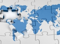 A world map puzzle with a piece on top, photo by Yuriy Panyukov/Adobe Stock