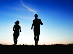 A silhouette of a jogger couple in sunrise, photo by LSOphoto/Getty Images/iStockphoto.