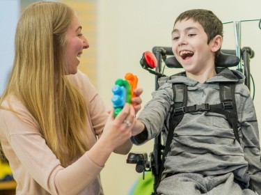 Caregiver playing with a young boy with special needs, photo by FatCamera/Getty Images