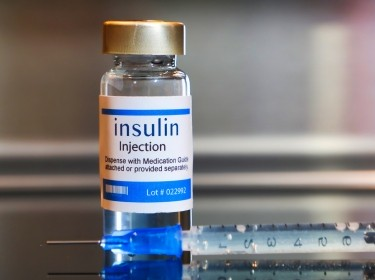 Vial of insulin with a syringe, photo by Bernard Chantal/Getty Images