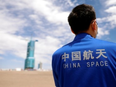 A staff member stands in front of the launchpad at Jiuquan Satellite Launch Center ahead of the Shenzhou-12 mission to build China's space station, near Jiuquan, Gansu Province, China, June 16, 2021, photo by Carlos Garcia Rawlins/Reuters