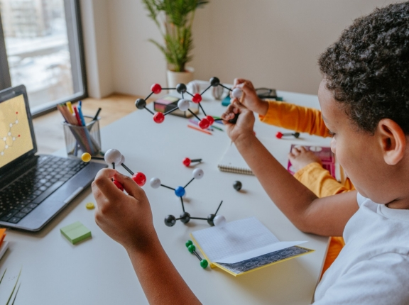 Student puts together molecular model during online school. lesson, photo by lithiumphoto/Adobe Stock