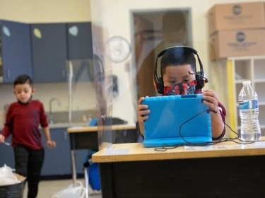 A student uses a tablet at a socially-distanced desk during a hybrid learning day at the Mount Vernon Community School in Alexandria, Virginia, March 2, 2021, photo by Tom Brenner/Reuters