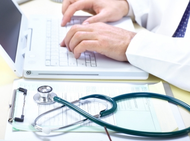 Doctor using laptop next to printed forms