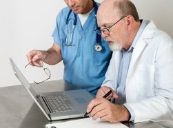 Two doctors with computer and paperwork