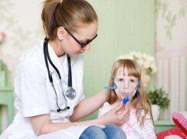 Doctor holding inhaler mask for girl breathing