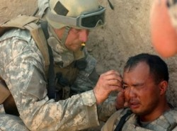 army medic treats a soldier wounded by shrapnel