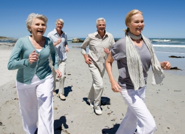 older couples jogging on beach